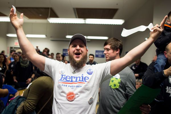 Aaron Miller, of Des Moines, cheers for Democratic presidential candidate Sen. Bernie Sanders (I-Vt.) during caucus night at
