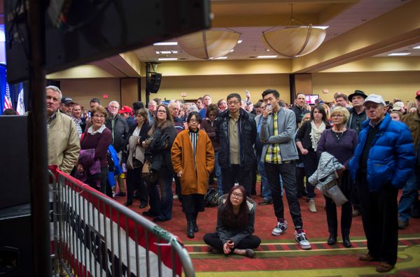Supporters of Republican presidential candidate Donald Trump watch as the first poll numbers come in to the Trump Caucus Watc