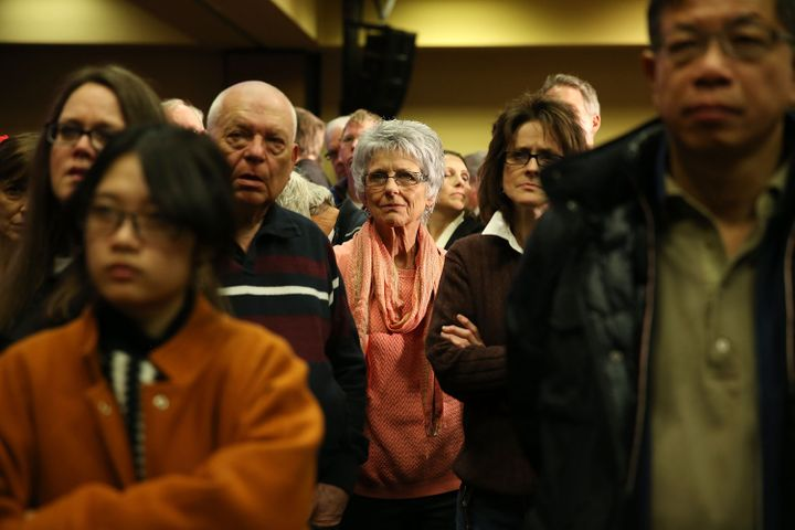 People watch a television showing the Caucus return numbers at the Donald Trump for President Caucus Watch Party at the Shera