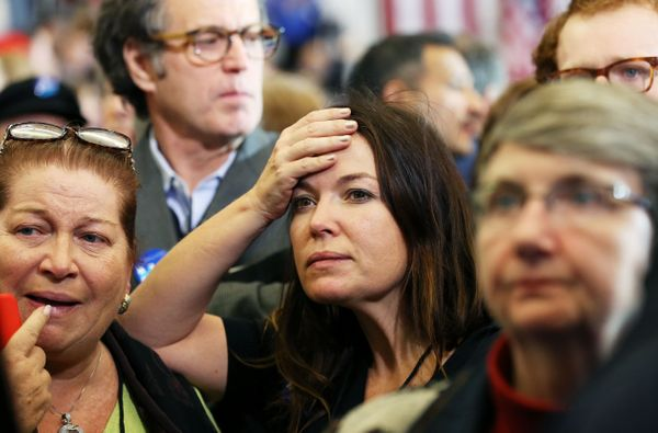 Supporters watch as results are displayed on a television during the caucus night event of Democratic presidential candidate