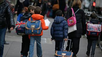 Children go to school early on November 16, 2015 in Paris, three days after the terrorist attacks that left over 130 dead and more than 350 injured. Reassure , explain, hold a minute of silence, schools are mobilized to welcome pupils and students, sometimes shocked or confused by the mass of information or rumors related to the attacks. France prepared to fall silent at noon on November 16 to mourn victims of the Paris attacks after its warplanes pounded the Syrian stronghold of Islamic State, the jihadist group that has claimed responsibility for the slaughter.  AFP PHOTO / KENZO TRIBOUILLARD        (Photo credit should read KENZO TRIBOUILLARD/AFP/Getty Images)