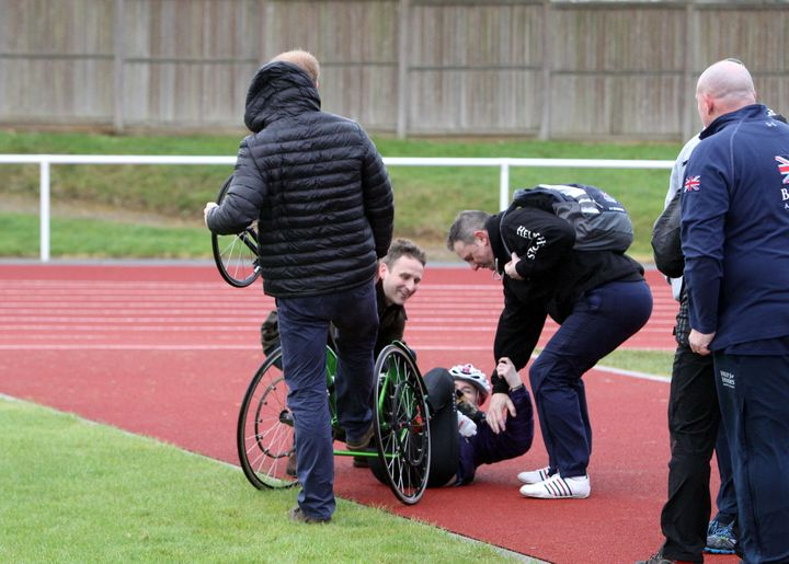 Prince Harry, with his back turned, helps Anna Pollock after she fell over during the UK team trials for the Invictus Games O