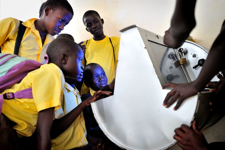 Young Ugandans gather around to use UNICEF's unique innovation the solar-powered Digital Drum, at Bosco Youth Centre in Gulu,