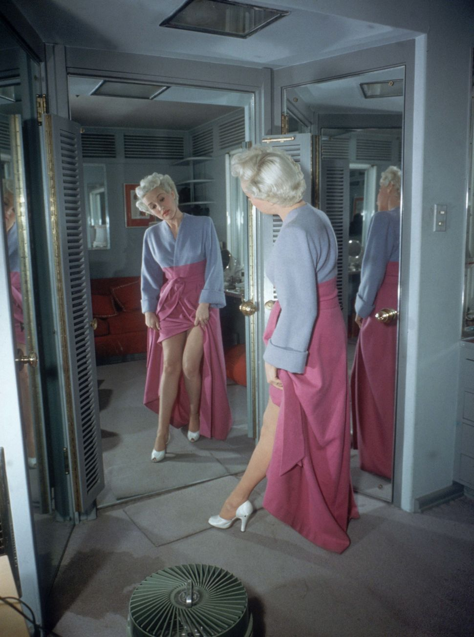 American actor and pin-up girl Betty Grable lifts her robe to look at her legs in a mirror on April 15, 1950.