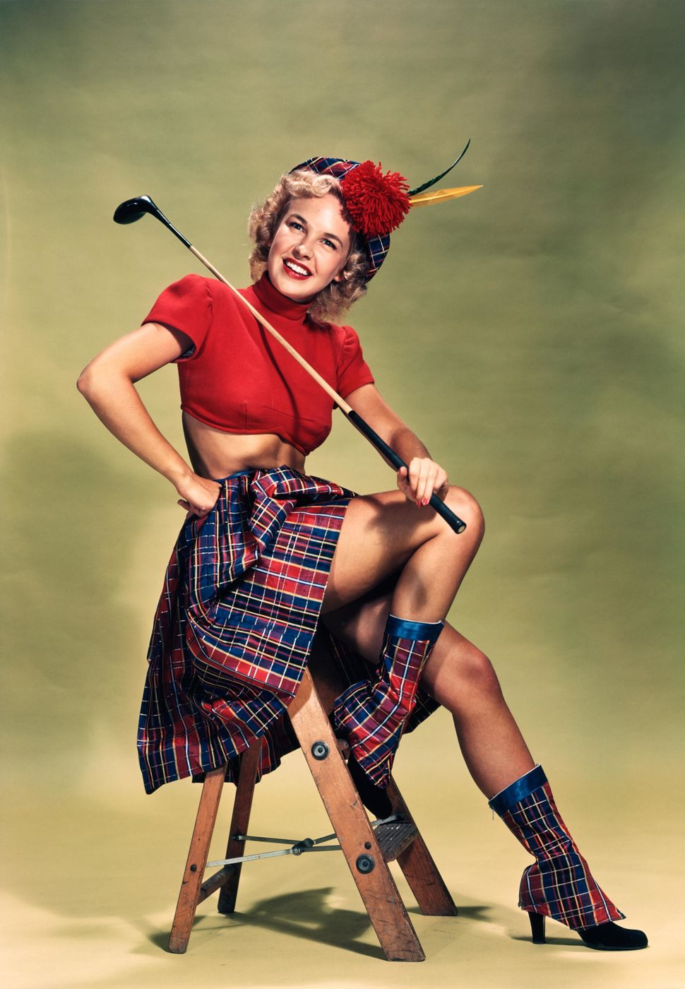 A 1949 pin-up portrait of a smiling blond woman wearing a red cropped sweater and plaid skirt whileholding a golf club.