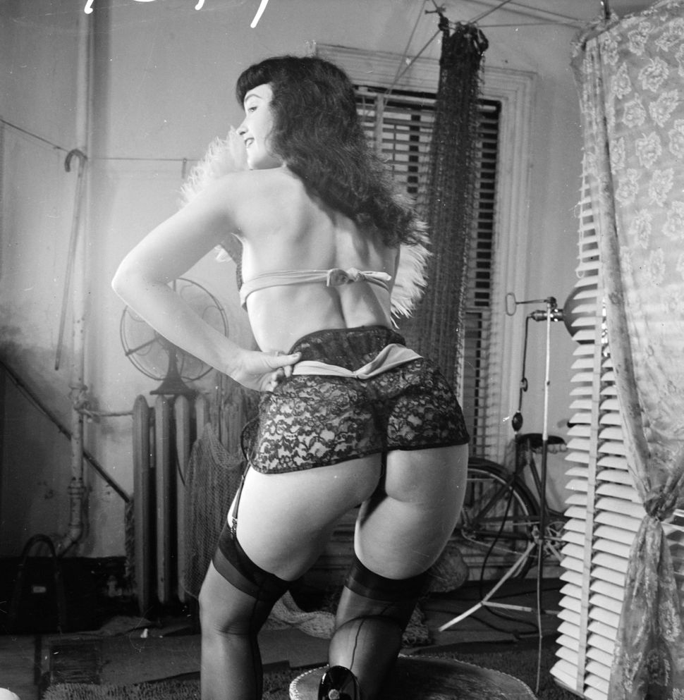 American pin-up Bettie Page, Playboy playmate of the month for January 1955, poses in a suspender belt.