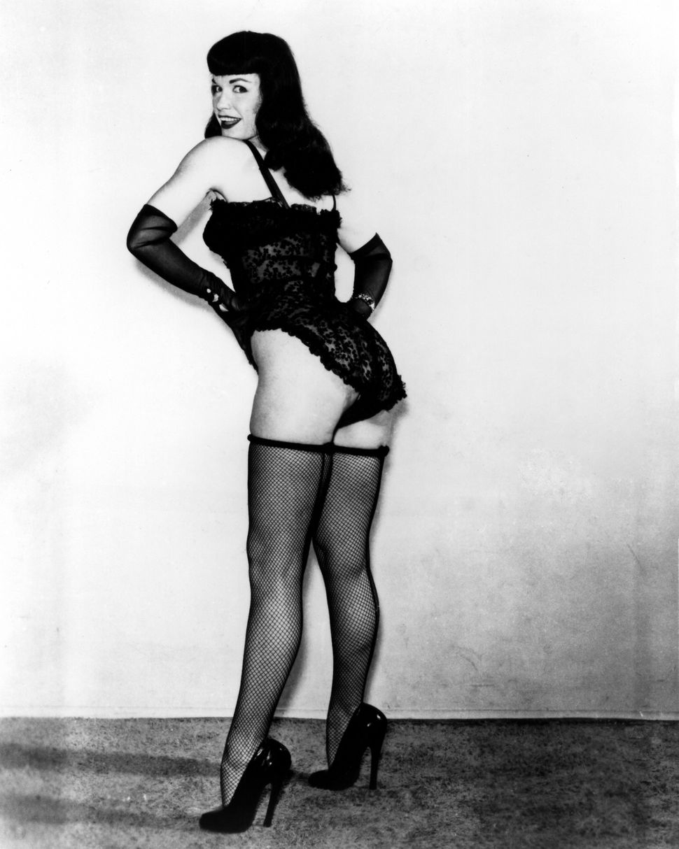 Pin-up model Bettie Page poses for a portrait wearing lingerie in 1952.