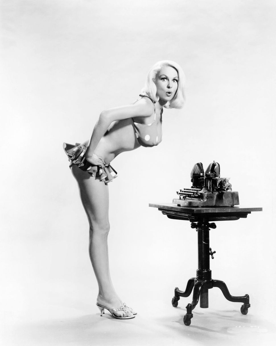 """American actress and pin-up model Joi Lansing is """"impressed by a typewriter"""" circa 1955."""