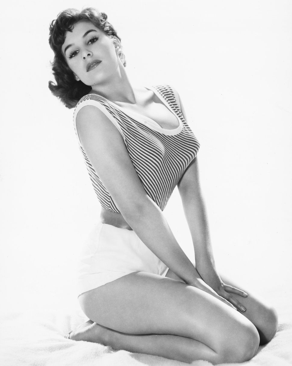 June Wilkinson, British actress and pin-up model, wearing a short, sleeveless and striped top with a scoop neckline, and a pa