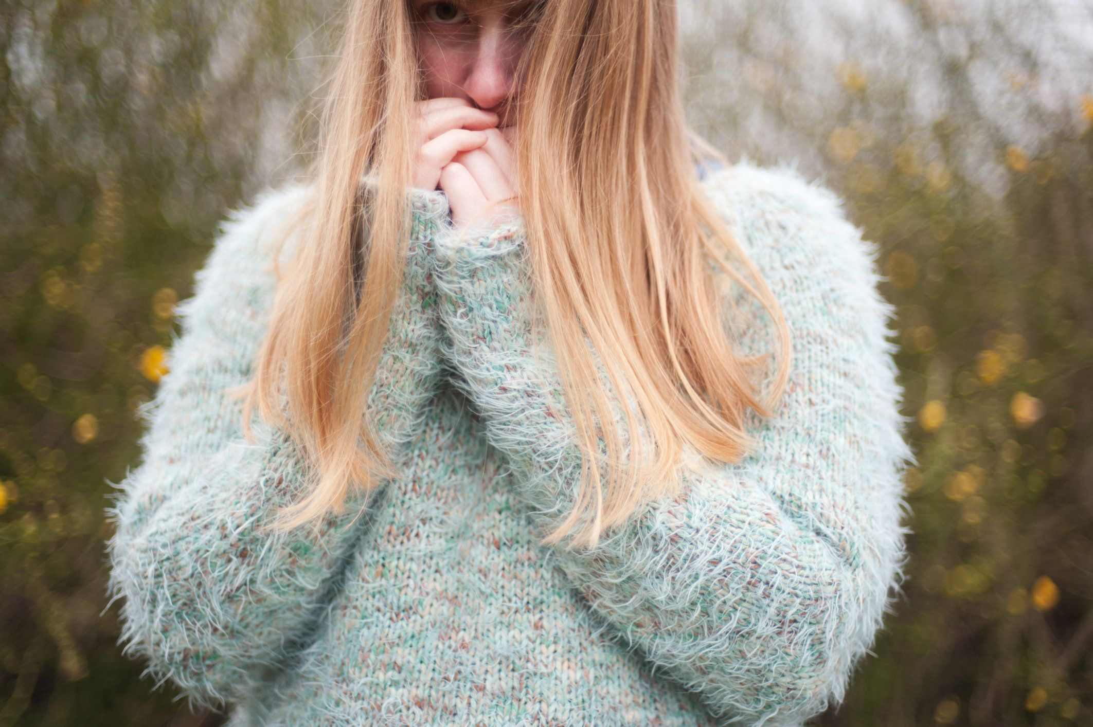 A young blonde woman wearing a fluffy, green jumper, stands outside with her hands in front of her mouth.