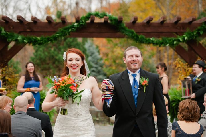Courtney Weber and her husband, Brian Hoover, walk down the aisle with their hands entwined by the handfasting cords.