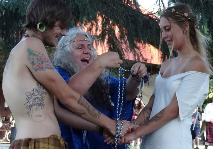 Selena Fox ties the handfasting cords during a couple's wedding ceremony at Pagan Spirit Gathering.