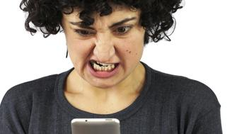 Angry young woman is looking at her phone and typing