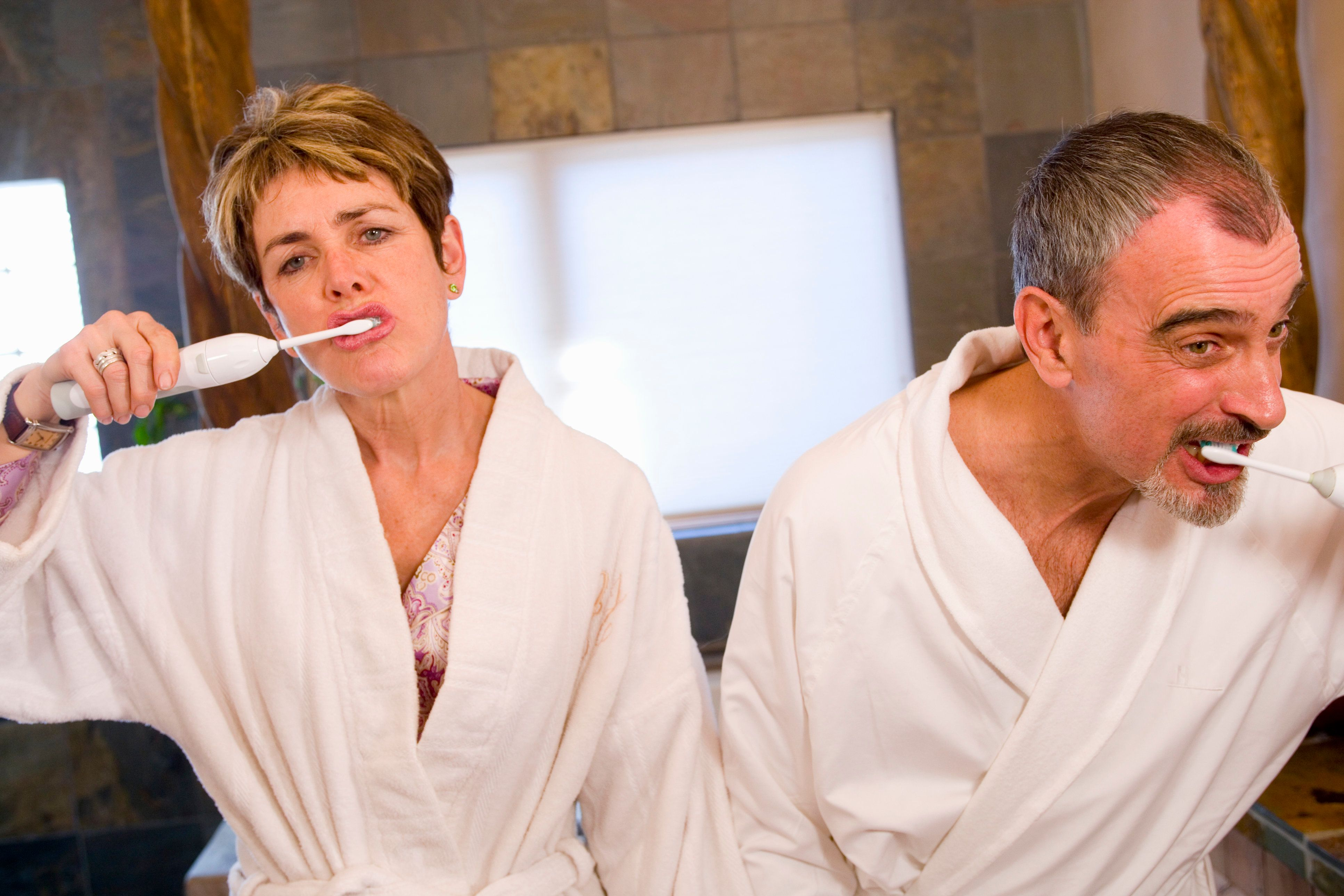 Mature couple brushing teeth together in bathroom