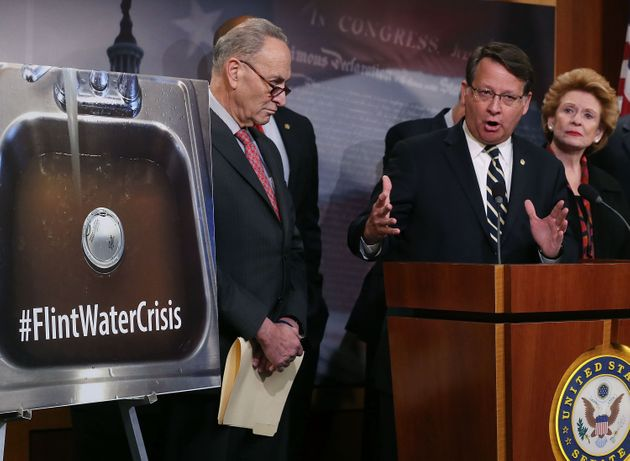 Flint's water crisis is finally in the national spotlight. Rep. Gary Peters (D-MI), center, flanked by...