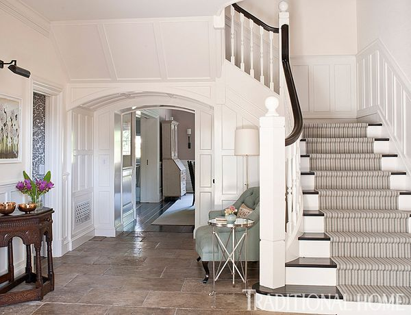 The home's all-white foyer instantly welcomes guests with an upbeat spirit and picture-perfect staircase.