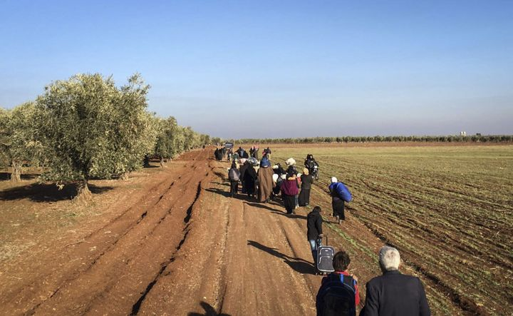 Syrians walk on a field as they migrate to Azaz region of Aleppo after Russian jets carried out airstrikes on opposition
