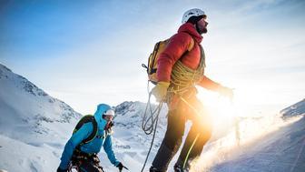 Mountain climber leading up a snowy ridge at sunrise.