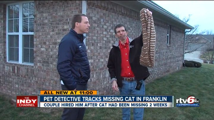Marmalade's owner holds up a blanket that was used to help find his missing cat.