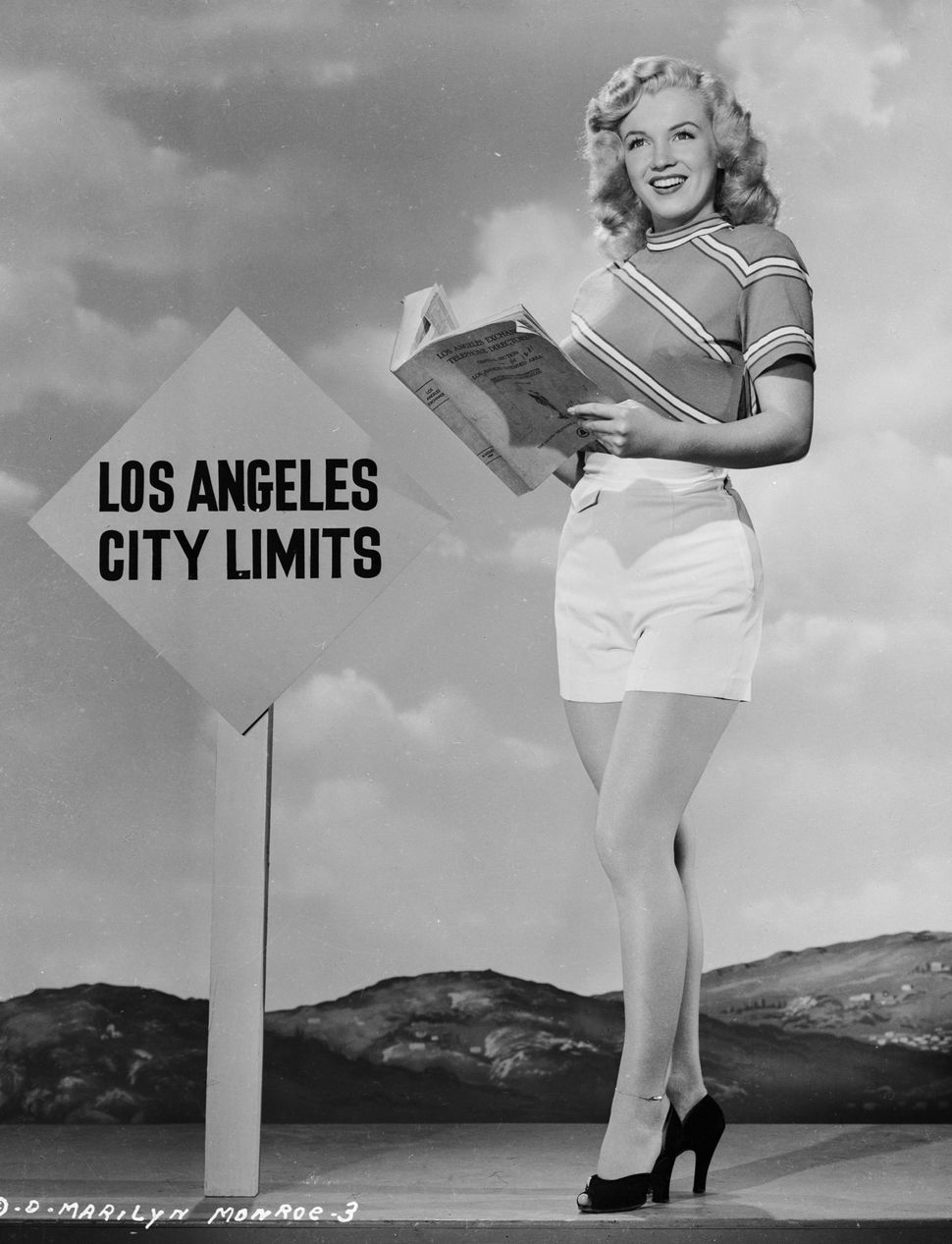 Marilyn Monroe reading an L.A. telephone directory near the Los Angeles city limits, circa 1947.