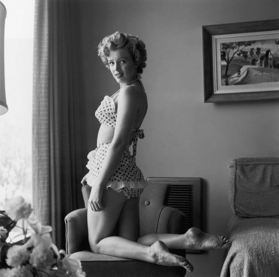 Marilyn Monroe kneeling in a chair in a two-piece polka dot bathing suit, circa 1951.