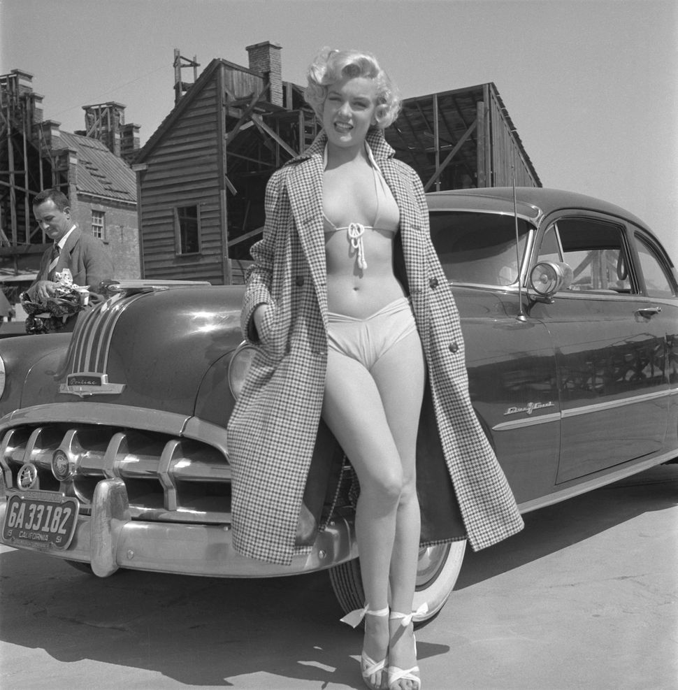 Marilyn Monroe poses for a portrait next to a 1950 Pontiac Chieftain on the backlot of 20th Century-Fox in 1951 in Los Angele