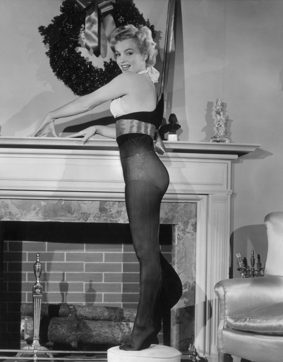 Marilyn Monroe poses while standing inside an oversized nylon Christmas stocking beside a fireplace, 1951.