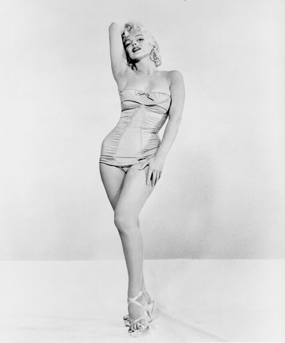 Marilyn Monroe poses for a portrait in a bathing suit with high heels, circa 1955.