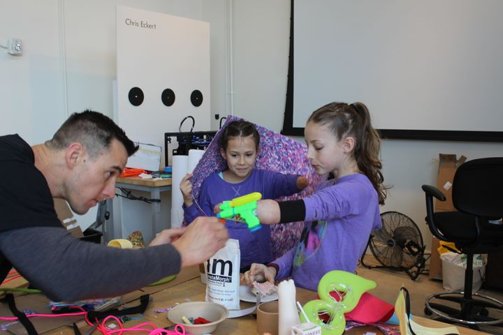 "Boatright helping Sydney design her ""dual water gun wearable"" activated by elbow movement that she created to hel"