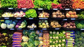 A display of fresh produce of vegetables and fruits in a grocery store supermarket refrigerator shelves case. A retail market environment. A large variety of food items are beautifully organize for the customer. Photographed on location in horizontal format.