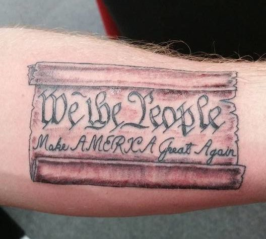 An image of the U.S. Constitution is see tattooed on someone's arm, along with Trump's campaign slogan.