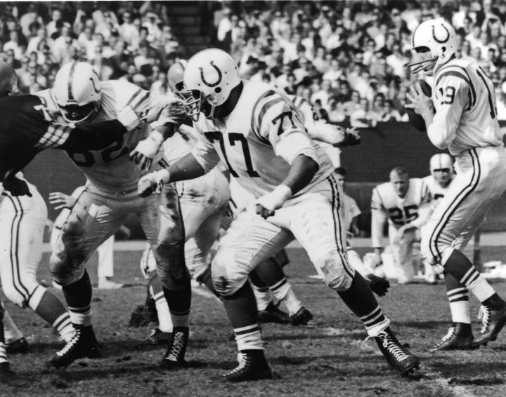 American professional football player Jim Parker (center), offensive tackle for the Baltimore Colts, blocks an opposing player while quarterback Johnny Unitas prepares to throw the ball during a game, late 1950s or 1960s.