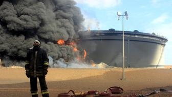 A Libyan fireman stands in front of smoke and flames rising from an oil storage tank at an oil facility in northern Libya's Ras Lanouf region on January 23, 2016, after it was set ablaze earlier in the week following attacks launched by Islamic State (IS) group jihadists to seize key port terminals. Firefighters battled the blaze at the oil facility for a third day, an official said, after an assault by jihadists aiming to seize export terminals.   / AFP / STRINGER        (Photo credit should read STRINGER/AFP/Getty Images)