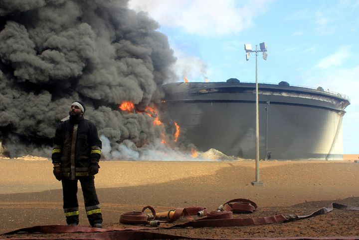 A Libyan firefighter stands in front of smoke billowing from an oil storage tank that was attacked by ISI