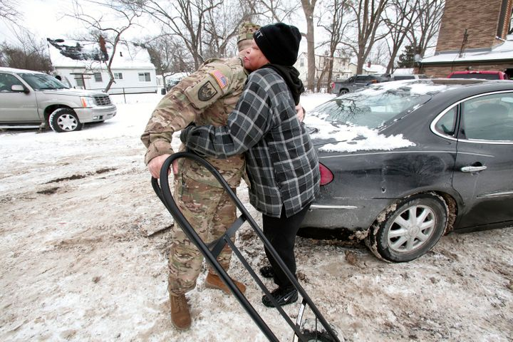 Christine Brown hugs Michigan National Guard Staff Sgt. Steve Kiger of Beaverton, Michigan,after he helped her take bot