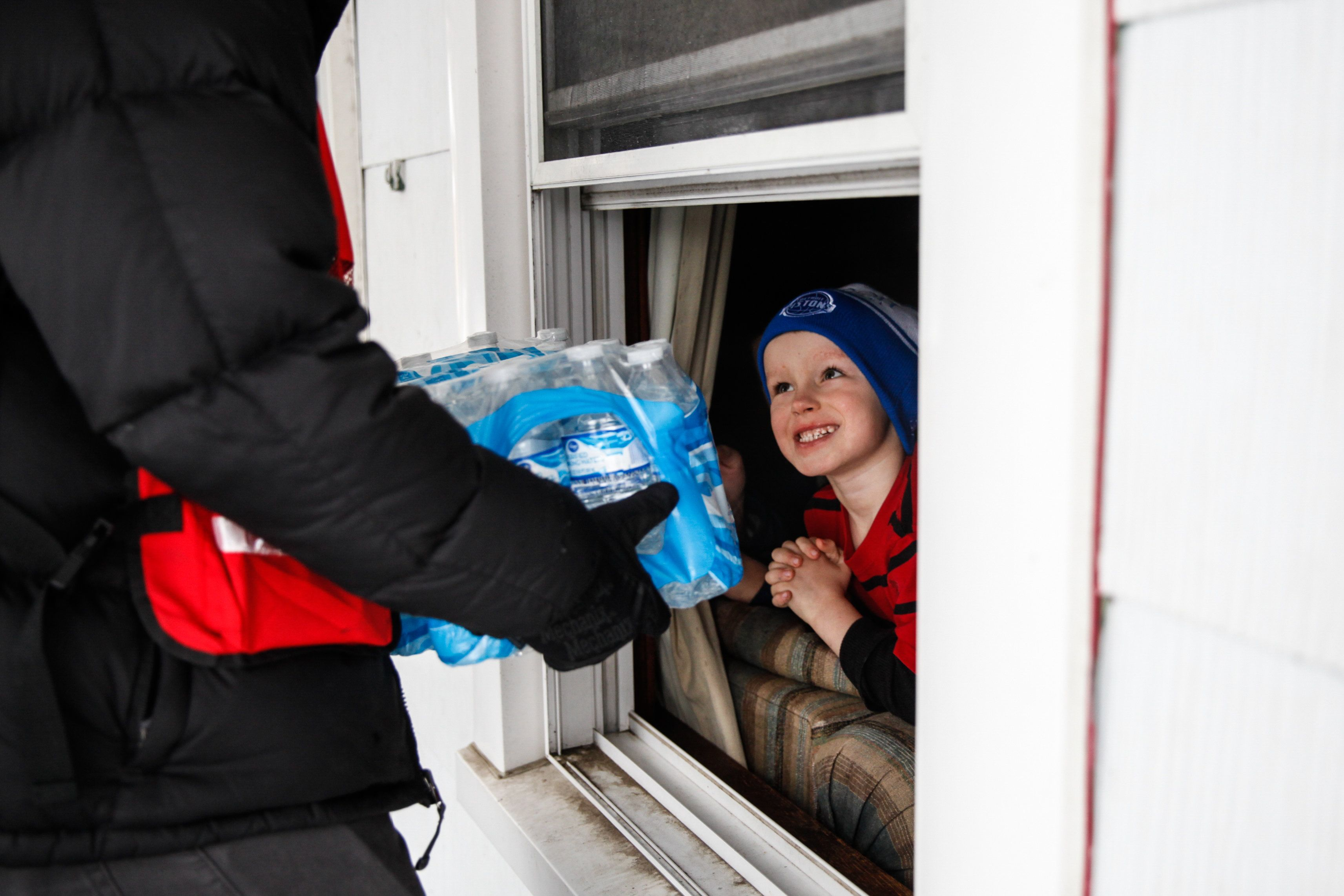 Jake McSigue, 6, receives a package of bottled water through the window of his grandma's home on Jan. 21, 2016 in Flint, Mich