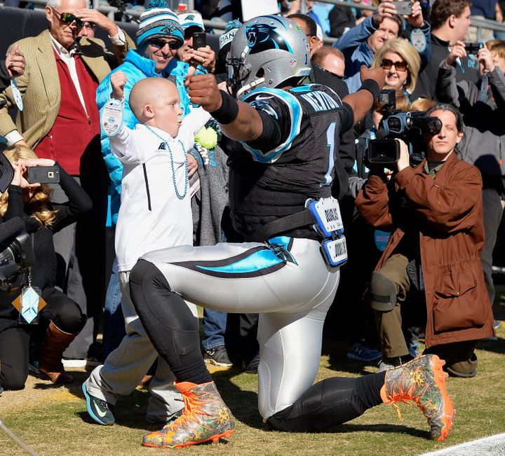 CHARLOTTE, NC - NOVEMBER 22: Cam Newton #1 of the Carolina Panthers greets a young fan before their game against the Washingt