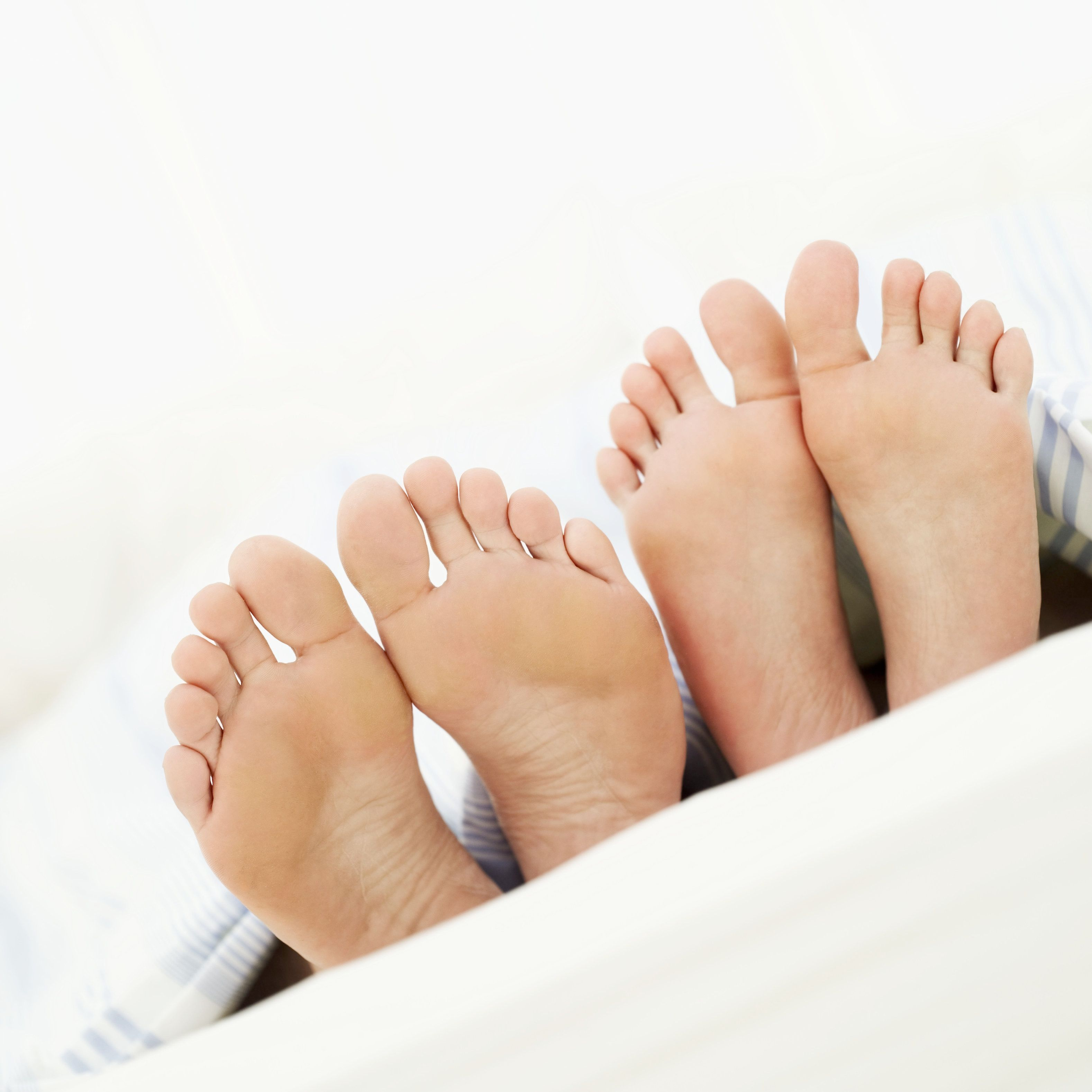close-up of the of a man and a woman's feet in bed