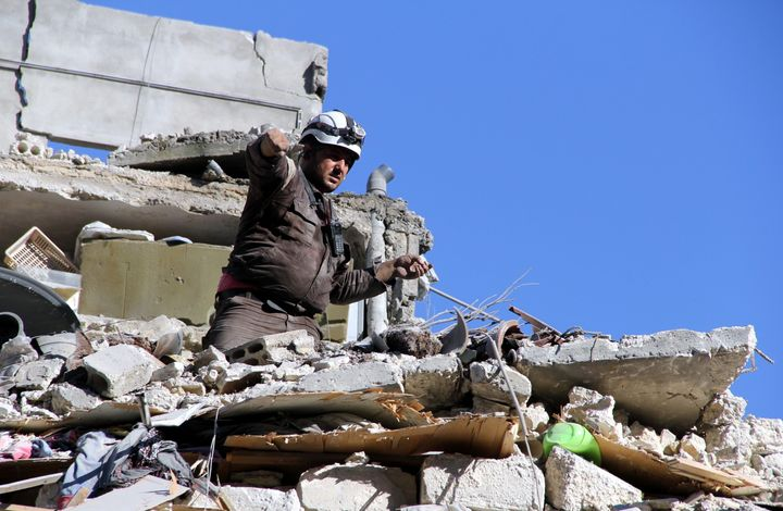 A man searches for survivors under the debris following Russian airstrikes in Aleppo.
