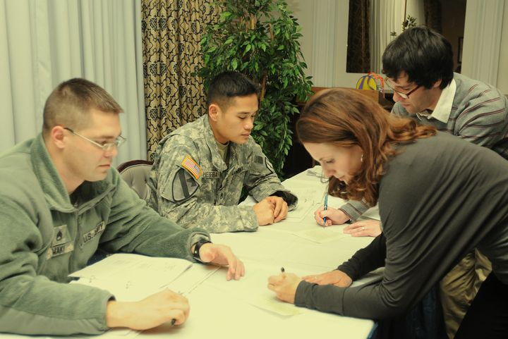 Facilitators from the University of New Hampshire sign the pledges of Staff Sgt. Oliver Herrera and Staff Sgt. Joseph Ma