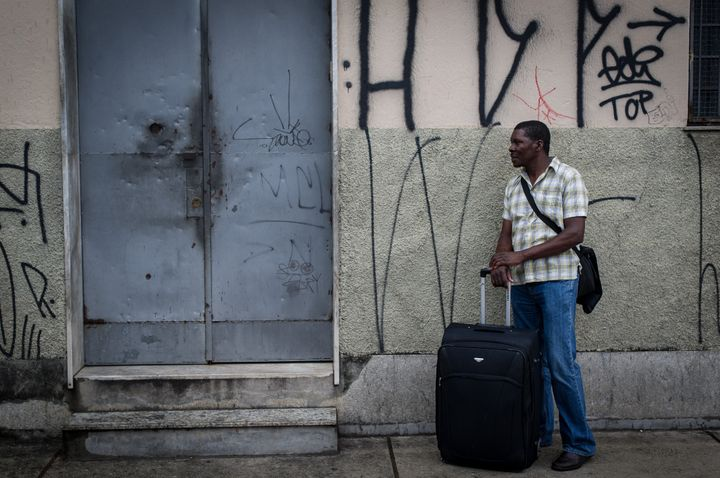 A Haitian man stands with his suitcase and waits at the entrance of a shelter for immigrants and refugees in Sao Paulo on Jan