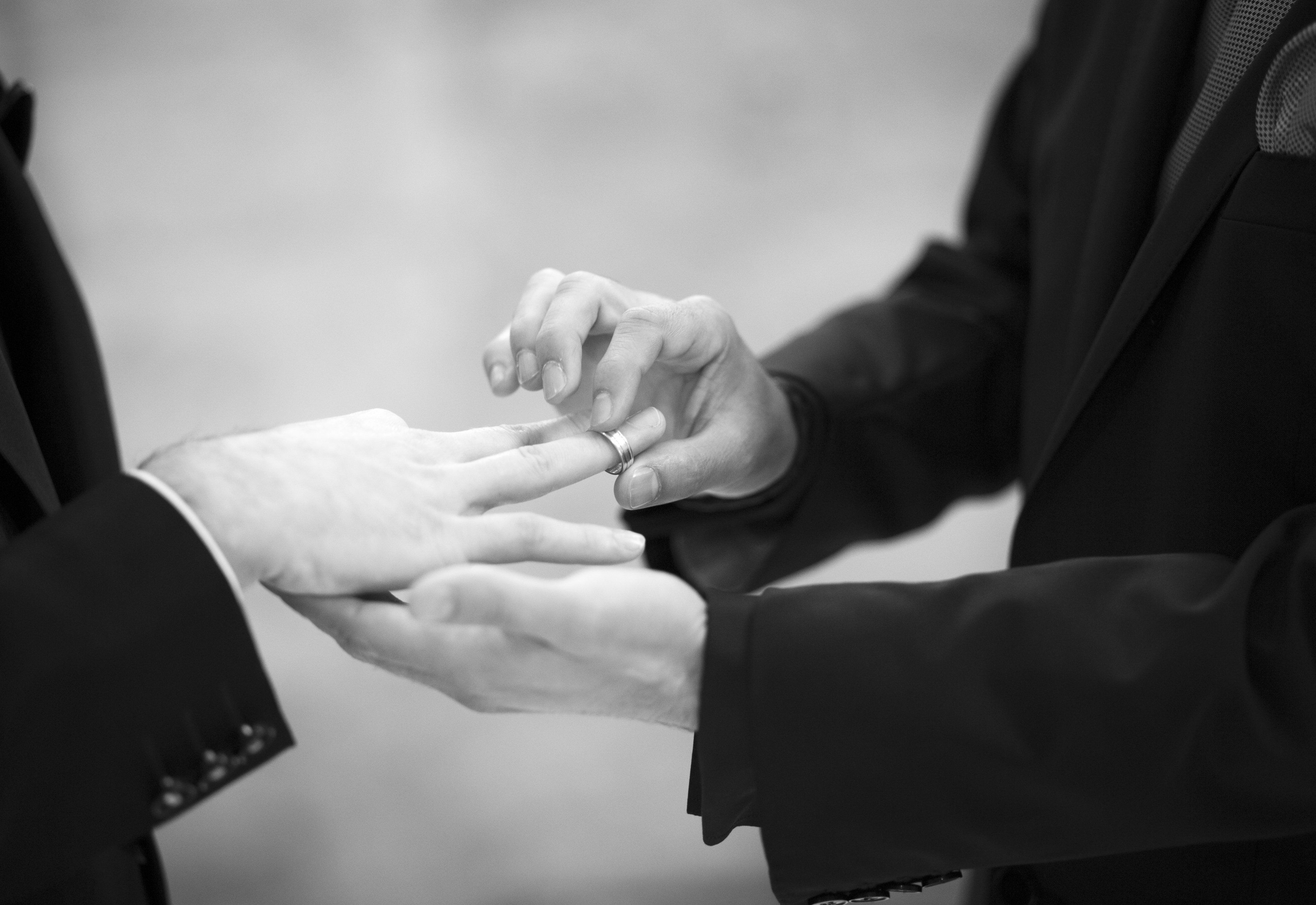 Black and white artistic digital rectangular horizontal photo of the hands of the two grooms wearing dark suits exchanging rings in a same sex homosexual gay wedding ceremony in Spain. Shallow depth of focus with background out of focus in bokeh blur.