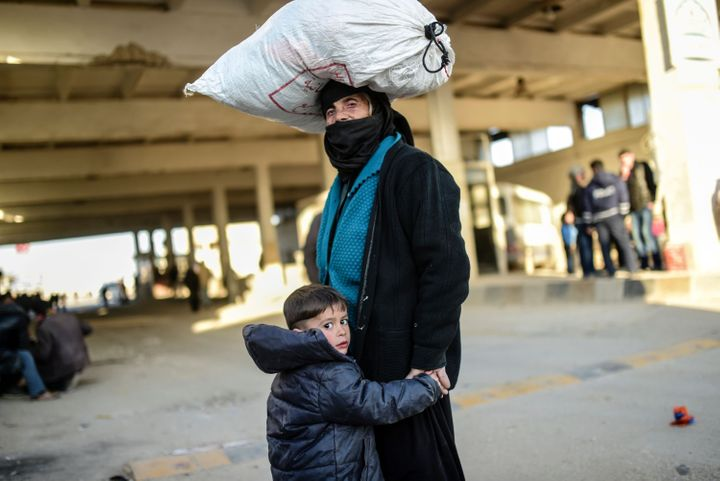 A woman and child wait at the Bab al-Salama border crossing between Syria and Turkey, which lies north of Aleppo, on Friday.
