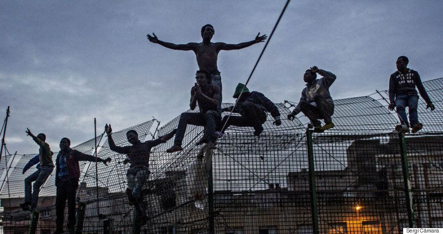A photo by Sergi Cámara documents an attempt by several men to cross the border fence separating M