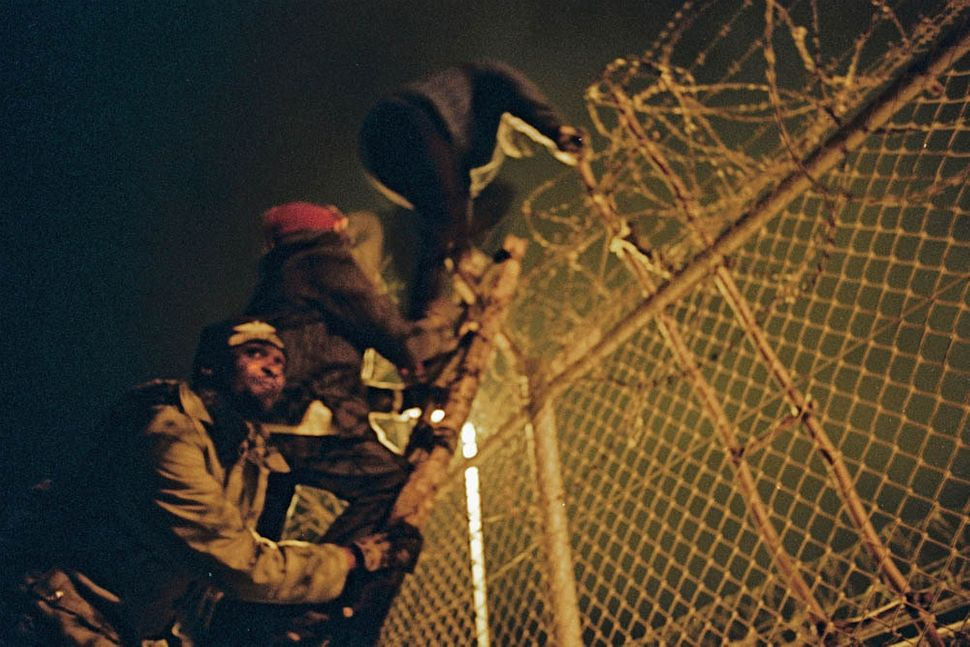 Men look out for police as they climb the fence separating Morocco and Melilla, a coastal Spanish town.