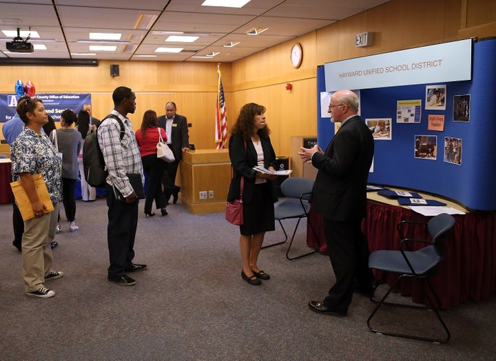 Job seekers line up to meet with a recruiter for the Hayward Unified School District in April 2013.
