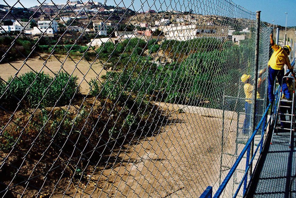 Workers heighten the fence to six meters in an attempt to keep migrants out of Melilla.