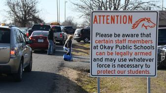 """New signs posted on the grounds of Okay Public Schools in Oklahoma announce an """"Armed School Employees"""" policy in place."""