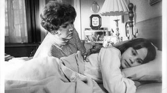 Ellen Burstyn reaches over Linda Blair who lays with head on pillow in a scene from the film 'The Exorcist', 1973. (Photo by Warner Brothers/Getty Images)