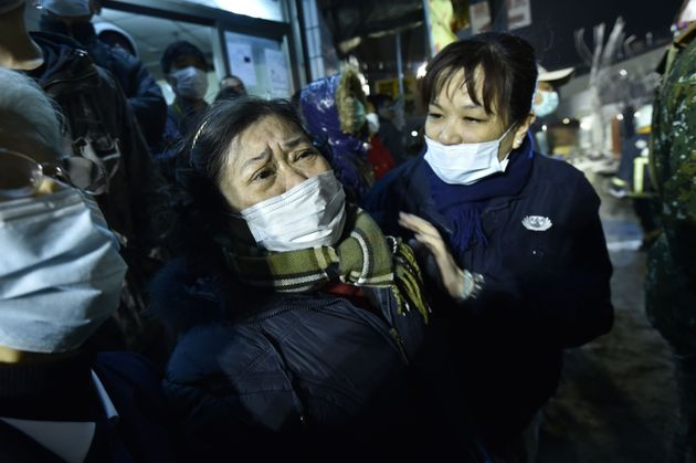A woman (C) is comforted as rescue personnel continue work at the site of a collapsed building in the...